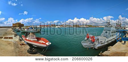 PAPHOS, CYPRUS - MARCH,  2016: Panoramic view of medieval Paphos Castle in Harbor with fishing boats in the foreground