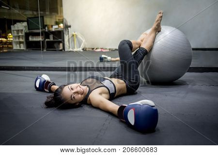 Young Asian happy woman wearing sportswear and boxing gloves laying on the floor with exercise ball in fitness gym excercise for healthy lifestyle concept