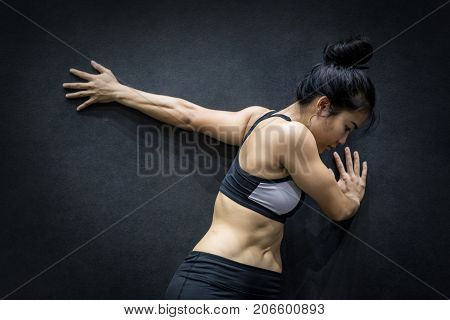 young asian woman wearing sportswear stretching her arm on black wall in fitness gym exercise for healthy lifestyle concept