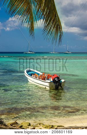 Beautiful exotic Caribbean coast with moored white motorboat, Dominican Republic, Caribbean Islands, Central America