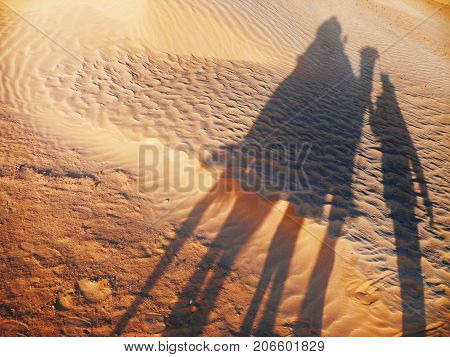 Shadow of tourist on camel and bedouin on sand. Sunset in Sahara desert. Tunisia.