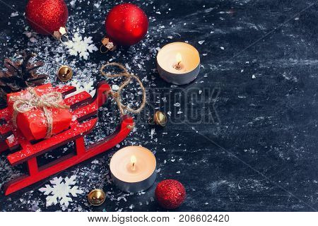holiday christmas new year black shabby background red toy sled balls gift box snowflakes bells free space for text
