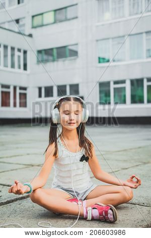 little girl sitting and listening music with headphones, pretty teen in a light sweater with a black bow listening to music on headphones