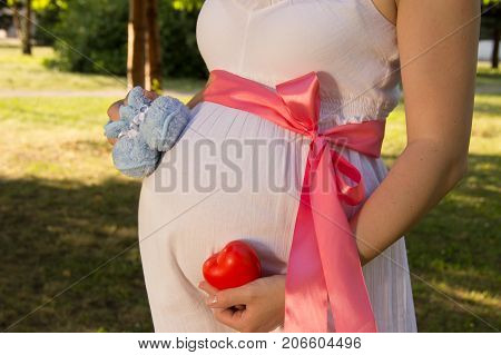 Belly of pregnant girl in white summer dress in park with blue booties red ribbon on belt and heart and clock on hands