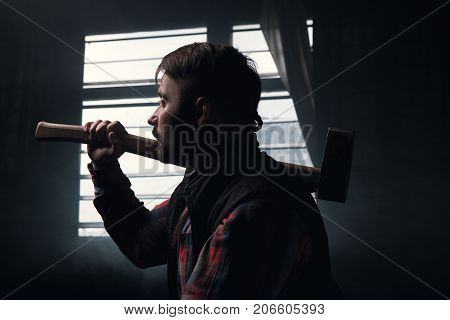Thoughtful woodsman with axe focus on foreground. Pensive lumberjack in dark room, hard craftsmanship work, male strength background