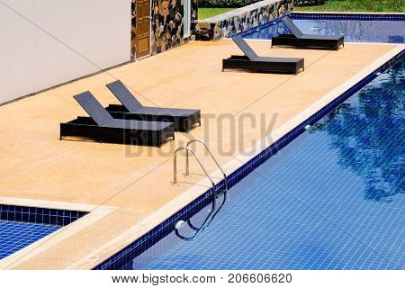 Black wicker daybed beside the swimming pool.