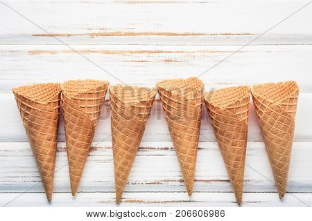 Flat Lay Ice Cream Cones Collection On White Wooden Background . Blank Crispy Ice Cream Cone With Co