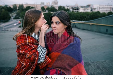 Two young girls gossip of somebody, close up. Spending good time together, modern urban life, communication and sale news, secrets and confidence concept poster