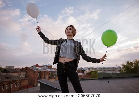 Enigmatic young woman with two toy balloons. Dreamy and infantile personality, airiness and hope, fly to dreams and rich imagination concept. Uban city background, free space