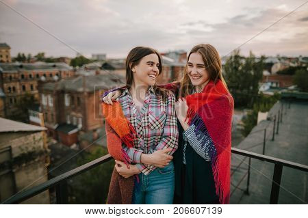 Couple smiling girls staying on city background. Spending good time together on roof, rest and entertainment, family and best friends forever concept. Free space
