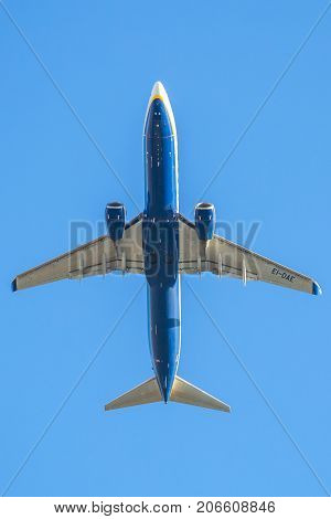 Bologna, Italy - December 20, 2016: low angle view of a Ryanair plane against sky, close up fling. blue Ryanair, low cost flights company, passenger airplane flight against blue background below view.