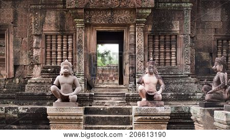 Two Hanuman statues guard the entrance of the Khmer temple in Angkor Wat park Cambodia.