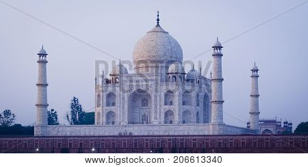 The Taj Mahal Mausoleum in Agra India seen from the other bank of the river ner the Garden of the Moon at sunrise