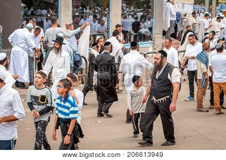 Hasids pilgrims in traditional clothes. The father leads the son by the hand. Uman Ukraine - September 21 2017: Rosh hashanah holiday Jewish New Year.