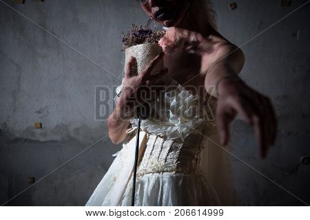 Bride Zombie in wedding dress with dried flowers pointing and want you to stay with her in abandoned house Halloween theme Ghost and deadman concept Heart broken and neglected concept Dark tone