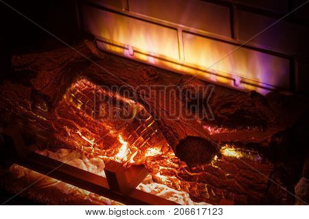 Electric Imitation of Fireplace with Firewood extreme closeup