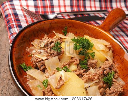 White cabbage with roasted beef and potatoes in a ceramic pan seasonal food