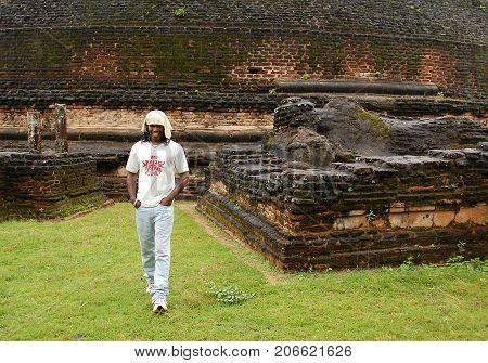 POLONNARUWA SRI LANKA - DECEMBER 5 2008: Smiling Sinhalese young man against the backgroubd of Pabalu Vihara stupa and reclining Buddha