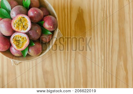 Passion fruit in wood bowl on wood table in top view flat lay with copy space for background or wallpaper. Ripe passion fruit so sweet and sour suitable make dessert. Passion fruit is tropical fruit. Passion fruit jam ready to served.
