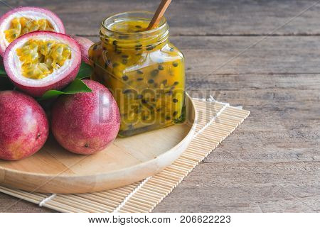Homemade passion fruit jam in bottle on wood plate. Passion fruit jam on wood table in side view with copy space for background. Fresh passion fruit and homemade jam on wood table in natural concept. Passion fruit jam ready to served.