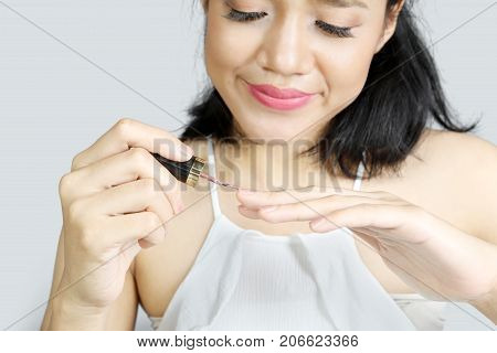 Picture of beautiful woman using nail polish on her fingernails. Shot with grey background