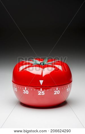 Tomato-shaped kitchen timer set at 25 minutes to fight procrastination in studying and working.