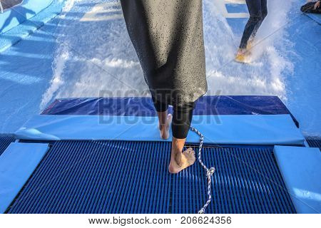 Bare foot coach in a suit for scuba diving training surfer against the background of a bright blue side of the pool and drops of water.