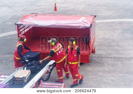 Udon Thani Thailand - September 16 2017 : Air Asia porters unloading luggage from the airplane after landing