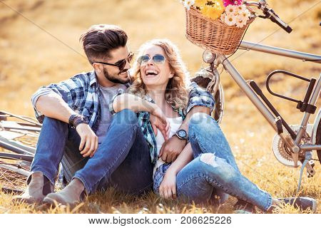 Young couple with bicycle in park. Couple in love sitting in park. Bicycle with flowers basket.