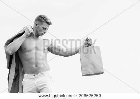 man with sexy muscular athletic strong body has bare torso and strong belly holding shopping bag with serious face on blue sky background