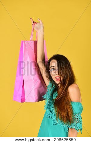 Lady Stands On Yellow Background Holding Pink Shopping Bag Up.