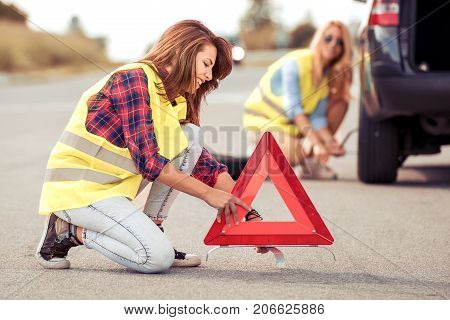 Two young woman on the road having problem with a car. Broken down car on the road.Traveling and transportation concept.