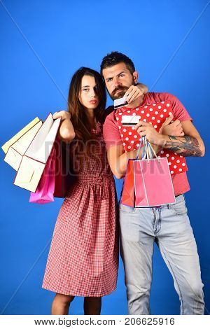 Couple Holds Shopping Bags On Blue Background And Hugs.