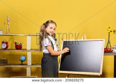 Girl Writes On Blank Blackboard, Copy Space