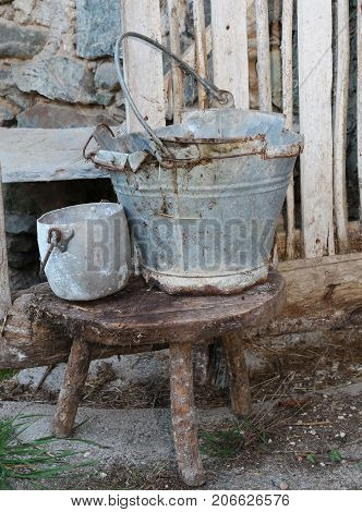 Broken Tin Bucket And An Pot Over The Stool Of The Old Stable