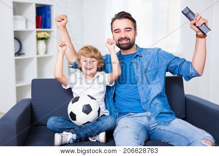 Happy Young Father And Son Watching Football And Celebrating Goal