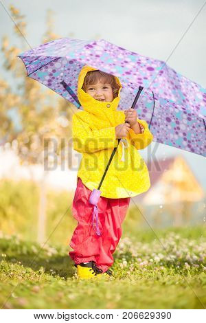 Child with colorful umbrella, wearing yellow waterproof coat and boots standing in the rain. Kid walking in autumn shower.