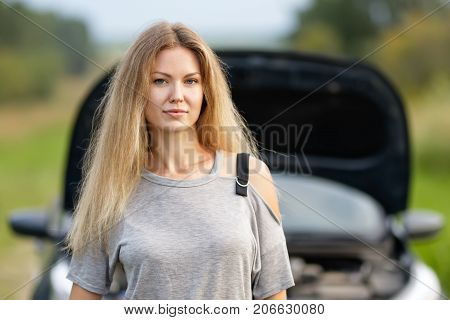 portrait of a girl near a broken car