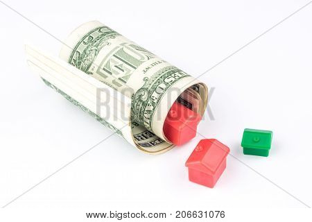 Two Small Red And One Green Houses Are Coming Out From Rolled Bunch Of Dollar Banknotes