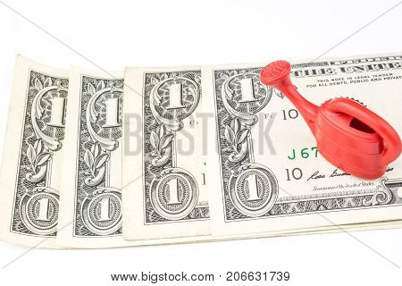 One Red Watering Can Laying On Four One Dollar Banknotes
