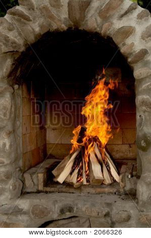 Brick Fireplace With Wood Fire Ready For Grill