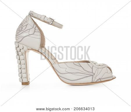 Beautiful female luxury leather white shoe, high-heeled, with décor, on white background, side view