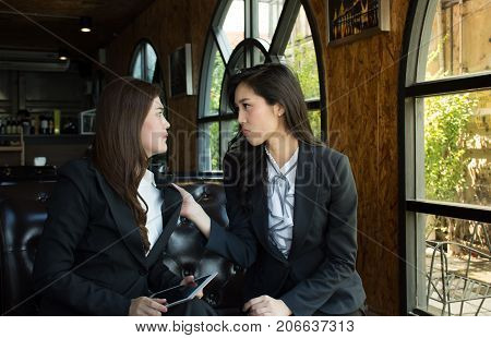 Portrait of Aggressive young Asian woman in formal wear or businesswoman fight in coffee shop/Two business woman have problem conflict, fighting, try to knock other one out