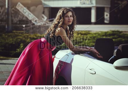 A beautiful young blonde woman in a luxurious pink evening dress outdoor near a cabriolet car.