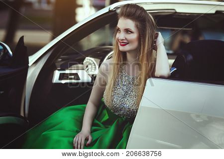 Portrait of a beautiful young blond woman in a luxurious green evening dress sitting in a car cabriolet.
