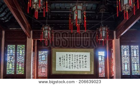 Shanghai, China - Nov 4, 2016: Traditional Chinese architecture and furnishings in the Feng Wu Luan Ying Hall. Featuring calligraphy in a hanging scroll. Low-light image.