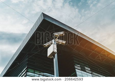 Close-up view of three security cameras looking in different directions on pillar with electrical box below; corner of modern glass and metal building in background (railway depot in Adler Russia)