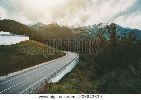 Beautiful autumn landscape with bending mountain highway bending after the hill overcast sky hills ridge in background overgrown with greenery and low rainy clouds Russia Estosadok district
