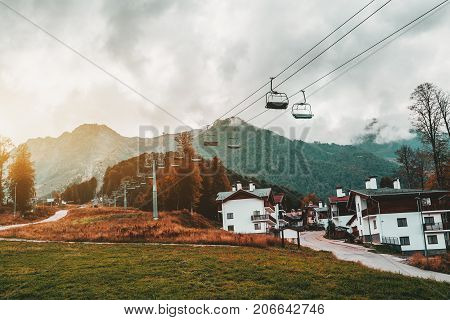Autumn landscape: cableway stretching into distance over hills with houses of resort village trees cell connection towers meadows and the road; low clouds Estosadok district Sochi Russia