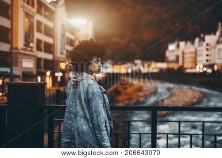 Beautiful curly afro-American lady with curly hair in jeans jacket with hood looking aside while standing on the bridge of Estosadok settlement with copy space place for text or your logo dusk